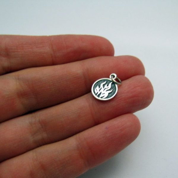 fire element tag front of charm sterling silver in hand to show scale